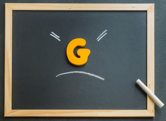Wooden G character on black board