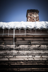 Brick chimney on the snow-covered roof of a wooden house. Toned