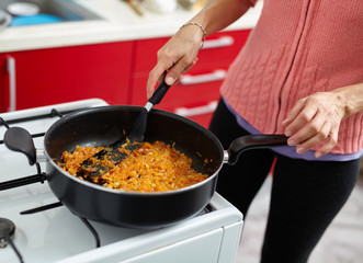 Woman cooking veggies in a pan