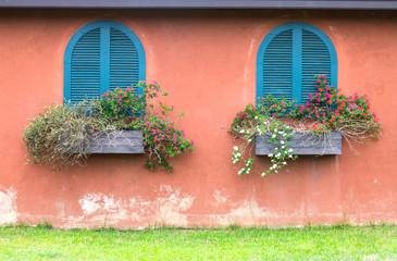 blue vintage window with wooden flower box on orange wall