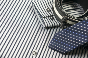 Tie and belt on striped shirt background