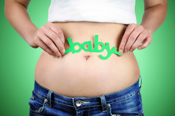 Baby word on woman´s stomach.