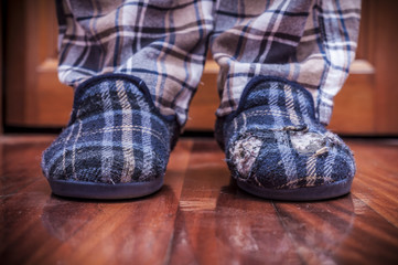 Man feet at home with broken slippers. Poverty