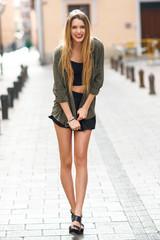 Happy blonde girl smiling in urban background
