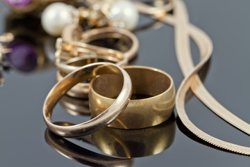 gold wedding rings, earrings and chains on a reflective surface