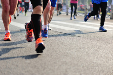 marathon athletes legs running on city road