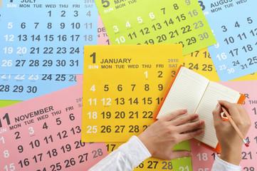 鉛筆を持った人間の手と2015年のカレンダー