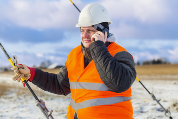 Electrical Engineer talking on cell phone near tensioner