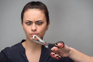 Addiction. Closeup of a hand with scissors cutting cigarette. Qu