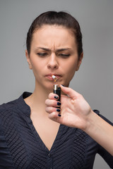 Closeup of woman smoking cigarette and a hand with lighter