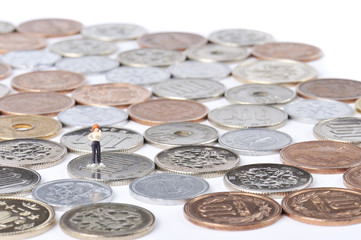たくさん敷き詰められた日本円硬貨の上に立っている人間