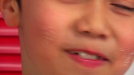 child licking sugar on his cheeks