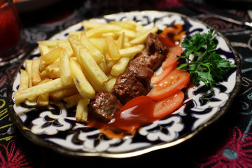 Veal kebab with tomatoes and fried potatoes