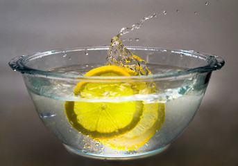 two lemon slices falling into bowl with water