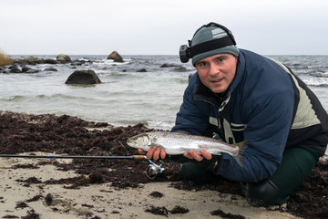 Portrait of angler with sea trout on the beach