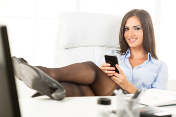 Sexy Businesswoman With Legs On The Desk
