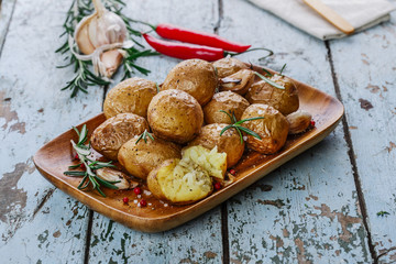 baked potatoes whole in their skins with rosemary and garlic