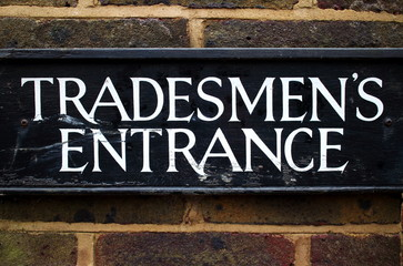 Tradesman Entrance Sign on a brick wall