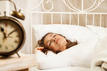 Woman sleeping in bed beside alarm clock