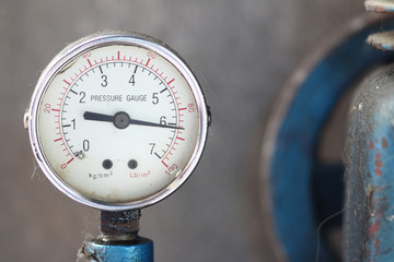 Close up pressure gauge with compressor.