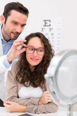 Optician helping out a woman to choose glasses