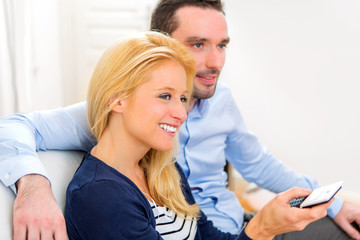 Young attractive couple watching tv