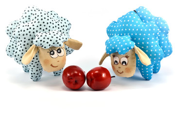 Two toy lambs with apples