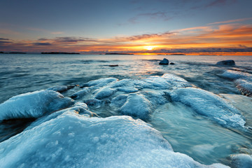 Ice covered rocks on the beach with sunrise