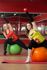 Girls lift dumbbells on fitballs
