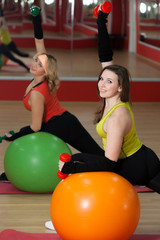Girls lift weights on fitballs