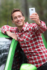 Driver by car taking selfie photo with smartphone