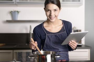 Hausfrau liest ein Rezept auf dem Tablet Computer
