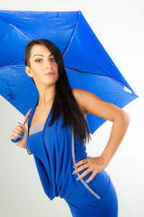 Sexy brunette surprised with blue ombrella