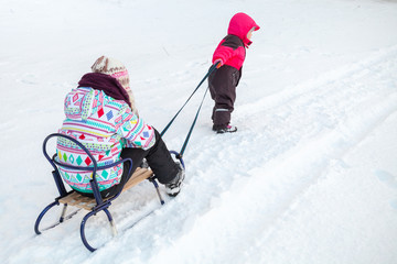 Little baby girl in pink pulling a sled with her sister
