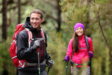 Hiking man and woman on hike in forest on hike