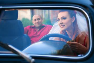 bride and groom in a retro car