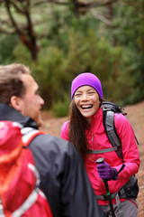 Couple having fun laughing hiking in forest