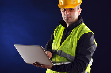 Young engineering with orange helmet working on a laptop