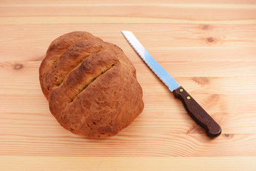Freshly baked loaf with a bread knife
