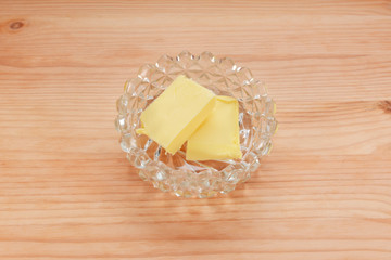 Two pats of butter in a glass dish