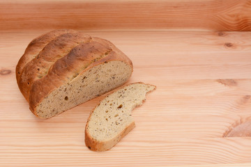 Half-eaten loaf of bread on a table with a cut slice