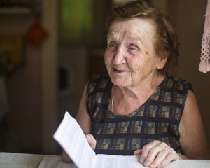 Old woman emotionally talks and reads in a notebook.