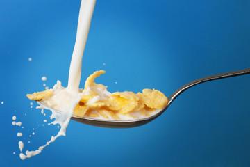 milk splashing into spoon with cornflakes