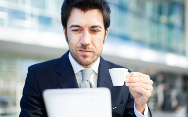 Businessman Using Laptop In Coffee Shop
