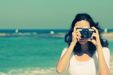 Woman with vintage retro camera having fun on the beach on blue