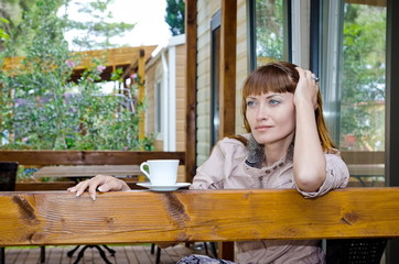 girl with white cup on the veranda of the house