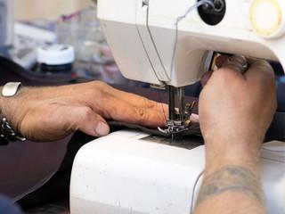Manos de un hombre manejando una maquina de coser