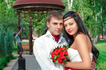 Bride and groom posing in amusement park