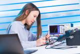 Girl repairing electronic device on the circuit board