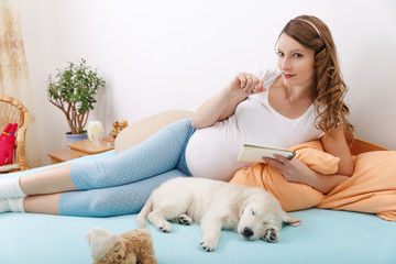Pregnant woman with her dog at home